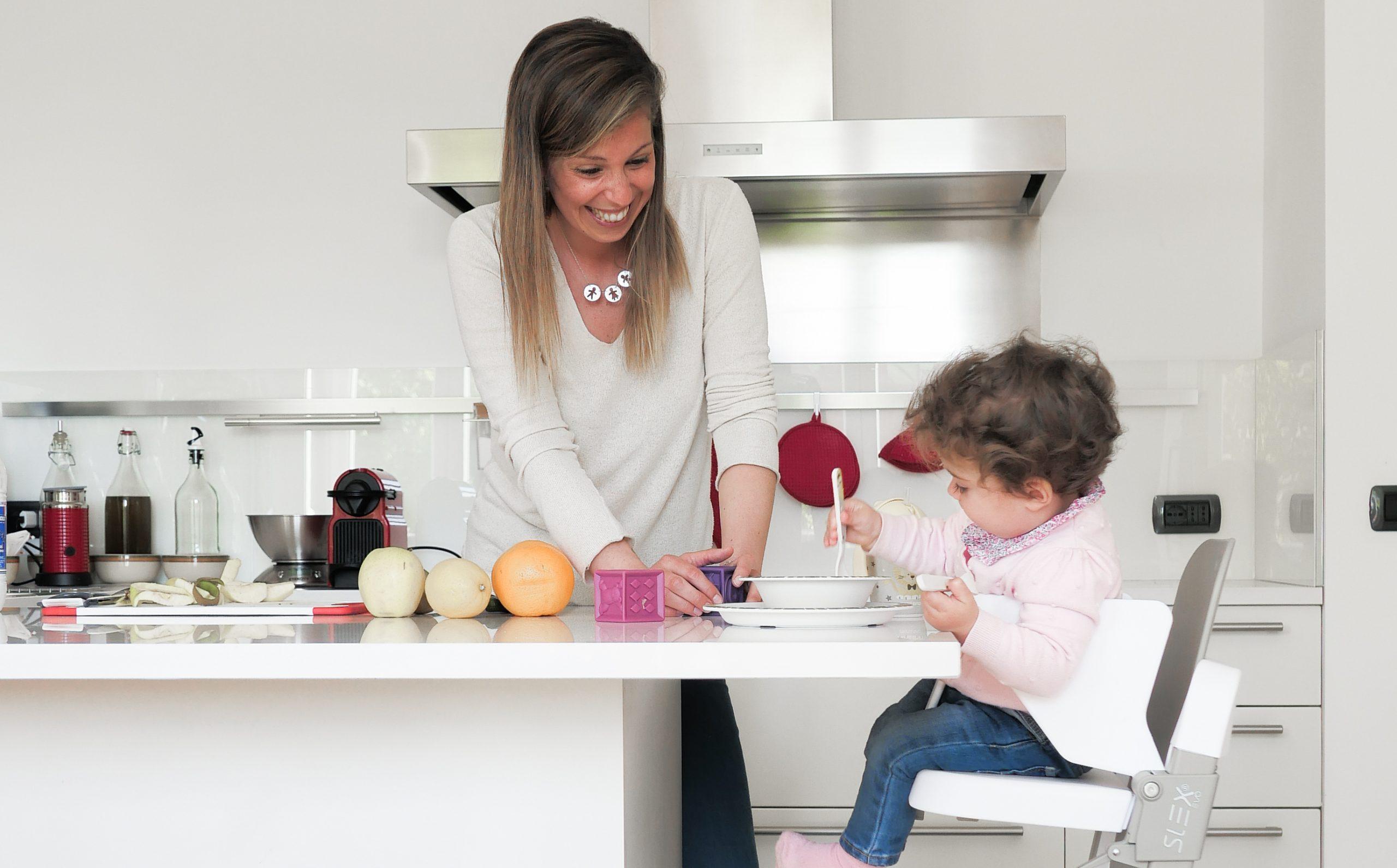 mamma in cucina con il suo bimbo seduto sulla sedia pappa slex evo